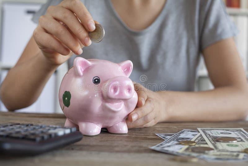 Sätta myntet i den piggy gruppen arkivbild