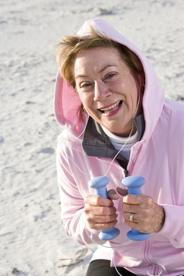 sätta på land öva kvinnan för handpensionärvikter arkivfoto