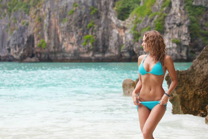 sätta på land bikinikvinnan arkivbild