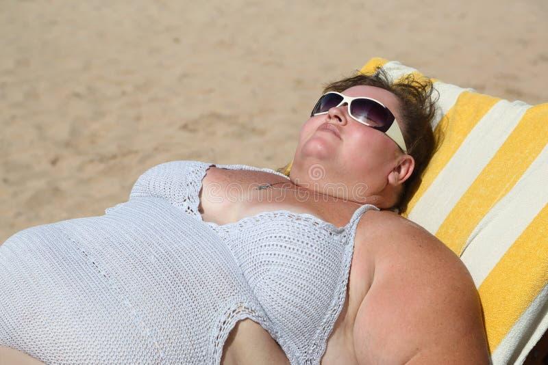 sätta på land den överviktiga kvinnan royaltyfri foto