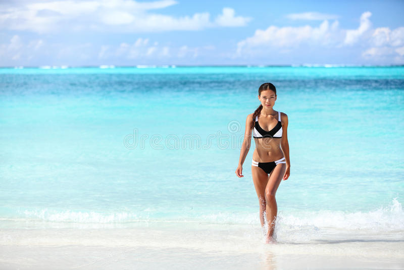 Sätta på land den asiatiska kvinnan för den sexiga bikinin som kommer ut ur vatten arkivfoton