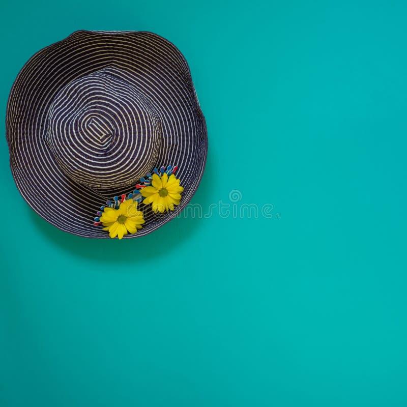 Sätta på land den blåa hatten som dekoreras med rolig solglasögon och, gulna blomman arkivbilder