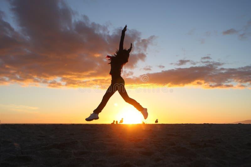 sätta på land den härliga solnedgångkvinnan royaltyfria bilder