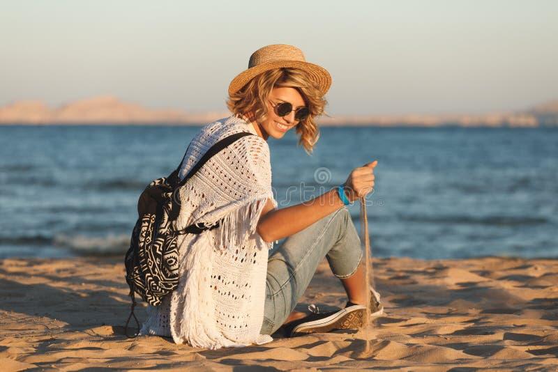 Sätta på land den lyckliga kvinnan och den bärande solglasögon och strandhatten som har sommargyckel under loppferiesemester royaltyfria bilder