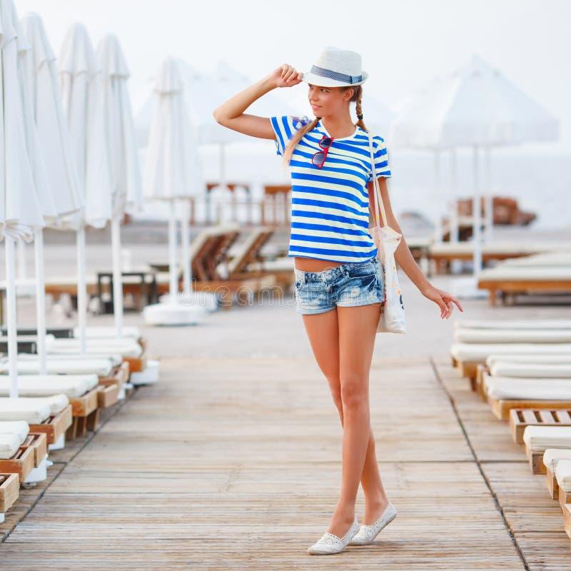 Sätta på land den lyckliga kvinnan och strandhatten som har sommargyckel under loppferier fotografering för bildbyråer