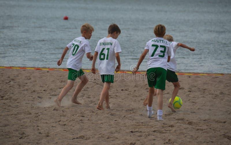 Sätta på land fotbollslaget av pojkar som spelar på sanden arkivfoto