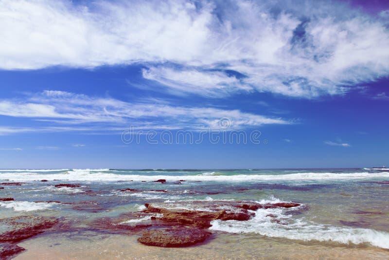 Sätta på land nära Mosselbay Sydafrika under morgonsolsken under en molnig himmel arkivbild