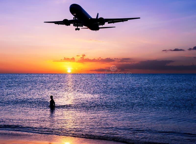 Sätta på land sand med flygplan- och himmelsolnedgång i skymning fotografering för bildbyråer