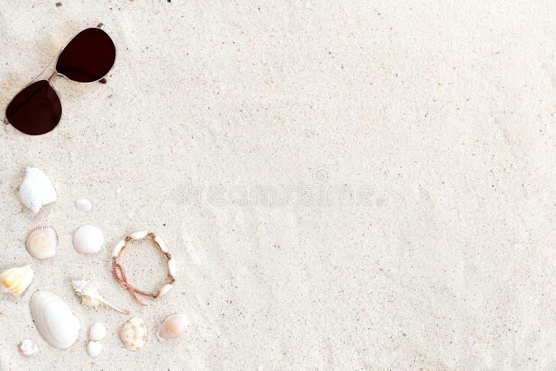 Sätta på land sand med solglasögon, skal och armbandet som göras av snäckskal fotografering för bildbyråer