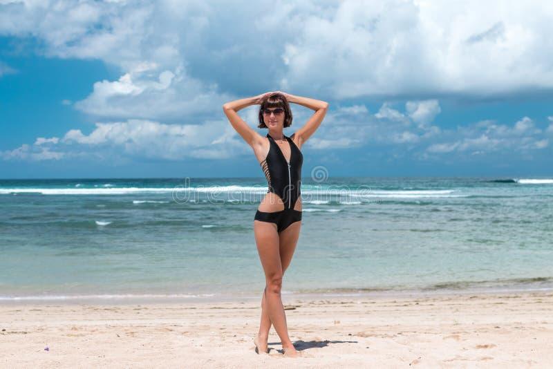 Sätta på land semestern Lycklig kvinna som tycker om solig dag på stranden Öppna armar, frihet, lycka och salighet Tropiskt begre royaltyfria foton