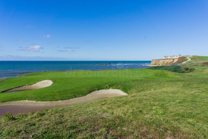 Sättande gräsplan för golfbana på klipporna vid Stilla havet, semesterort i bakgrunden, Half Moon Bay, Kalifornien royaltyfria bilder