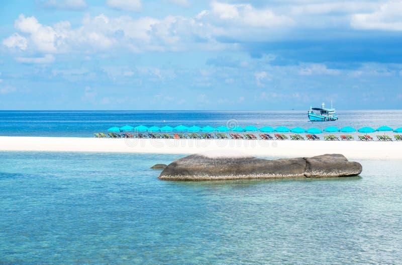 Sätter på land blå himmel för det härliga tropiska strandblåtthavet och vitsand med den strandstolar och slags solskydd för somma royaltyfri fotografi