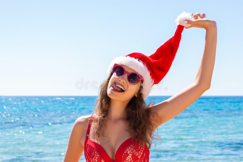 Sätter på land den unga kvinnan för solbränna som är slank i den santas hatten, och avslappnande tropisk sand för röd baddräkt be arkivfoton