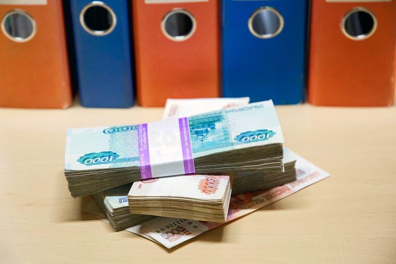 Sätze Geld auf dem Hintergrund von farbigen Geschäftsordnern lizenzfreies stockfoto