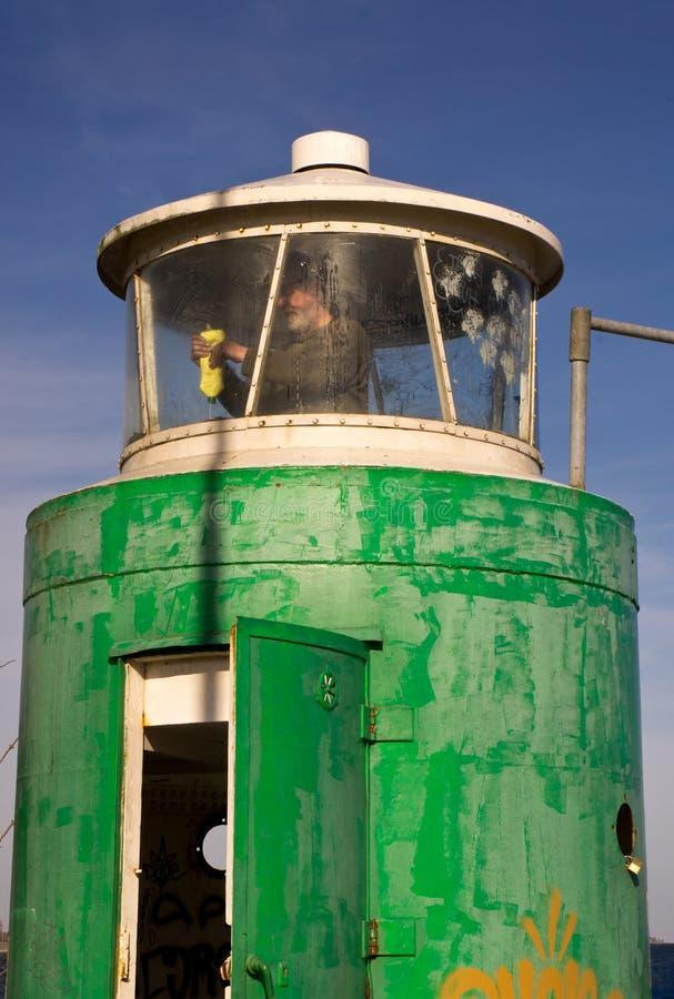 Säubern der Fenster des kleinen Leuchtturmes in Aarhus' Yachthafen, Dänemark lizenzfreies stockfoto