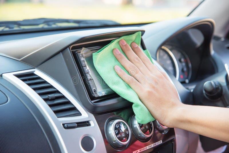 Säubern des Autoinnenraums mit grünem microfiber Stoff stockfotografie