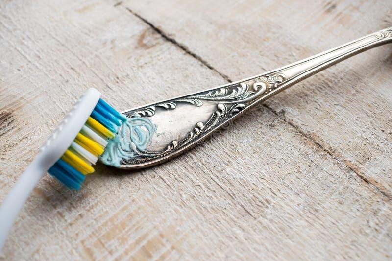 Säubern des Tischbestecks mit einer Bürste und einer Paste Verdunkeltes Reinigungss stockfotografie