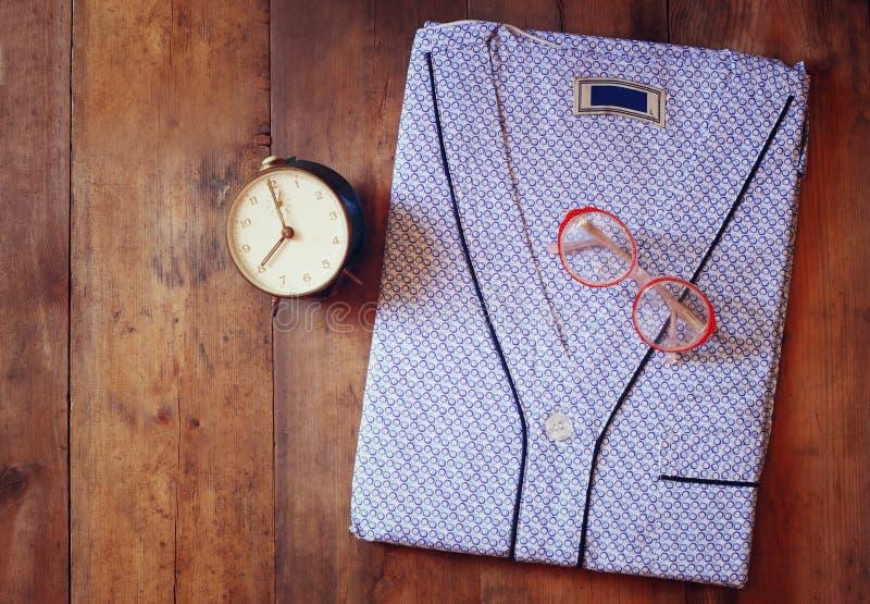 Säubern Sie den Pyjama des gefalteten Mannes, Weinleseuhr und Gläser über hölzernem Hintergrund Beschneidungspfad eingeschlossen lizenzfreie stockfotos