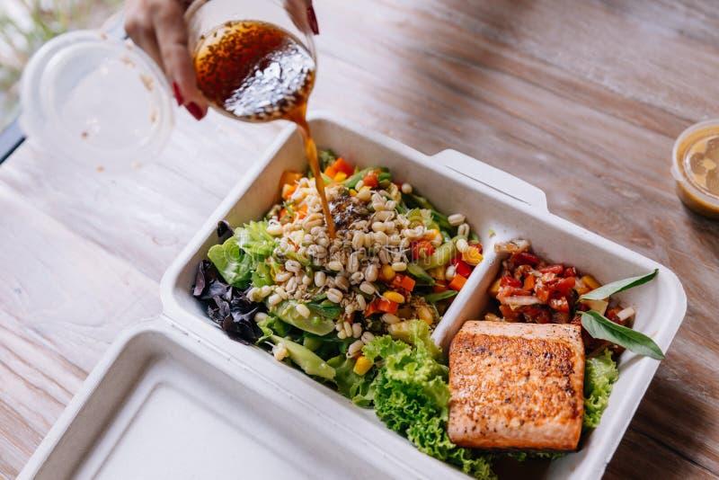 Säubern Sie Lebensmittelmahlzeitkasten: Strömende Salatsoße über gegrilltem Lachsfilet mit Tomate und Sojabohnensprossesalat eins lizenzfreies stockbild