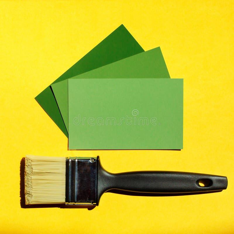 Säubern Sie Malerpinsel und drei Kartenproben von grünen Farben lizenzfreie stockbilder