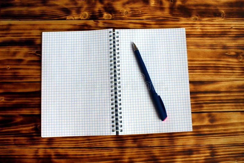 Säubern Sie offenes überprüftes Notizbuch mit blauem Stift stockfotos