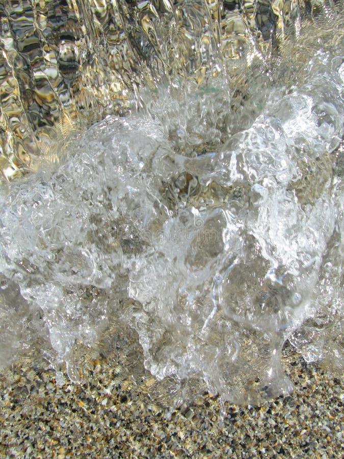 Säubern Sie Welle mit großen Blasen über kleinen Steinen von oben lizenzfreies stockbild