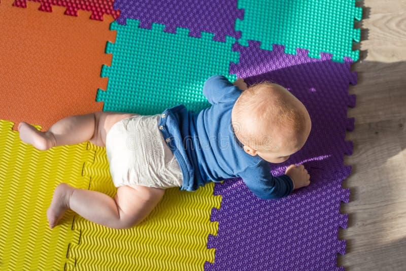 Säuglingsbaby, das auf bunter weicher Matte spielt Das kleine Kind, das zuerst kriechen macht, tritt auf Boden Draufsicht von obe stockfotos