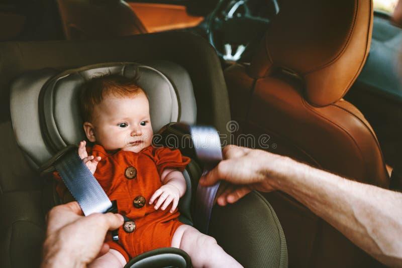 S?uglingsbaby im Sicherheitsautositz und -vater befestigt Gurt stockfoto