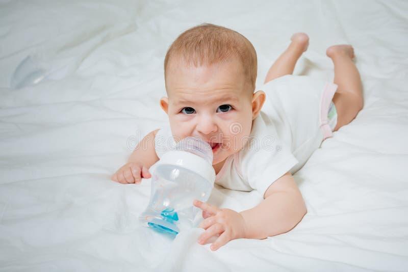 Säuglingsbaby mit den großen braunen Augen, die auf dem weißen Bett mit spezieller Flasche Wasser mit Nippel liegen Versucht, sie stockfotografie