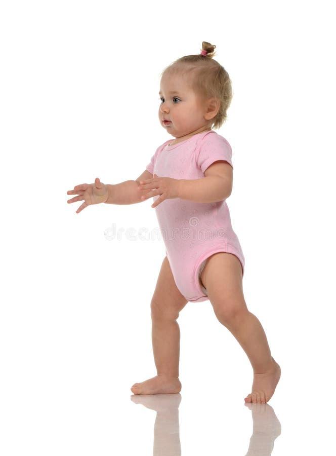 Säuglingskinderbaby-Kinderkleinkind im rosa Körperstoff machen zuerst stockfotografie