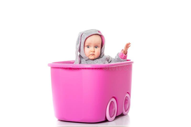 Säuglingsmädchen des hübschen Babys in einem Häschenkostüm, das innerhalb eines rosa Kastens auf weißem Hintergrund sitzt lizenzfreie stockbilder