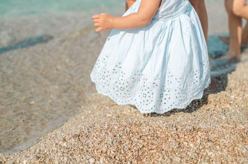 Säuglingsmädchen im blauen Kleid, das zuerst Schritte im Sand mit Mutterhilfe am sonnigen Strand unternimmt lizenzfreies stockfoto