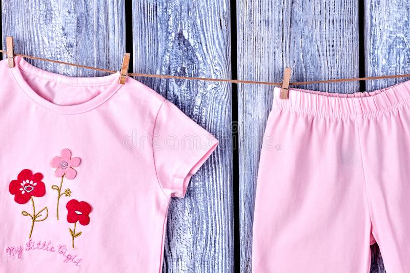 Säuglingsmädchenkleidung, die am Seil hängt stockfotografie