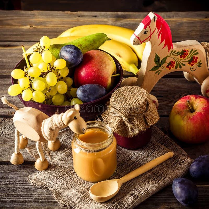 Säuglingsnahrung, Früchte und Spielzeug auf Holztisch stockfoto