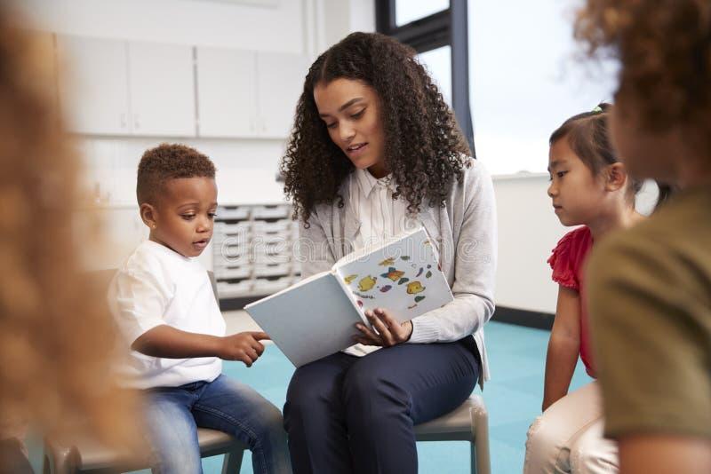 Säuglingsschuljunge, der in ein Buch gehalten vom weiblichen Lehrer, sitzend mit Kindern in einem Kreis auf Stühlen im Klassenzim stockfoto
