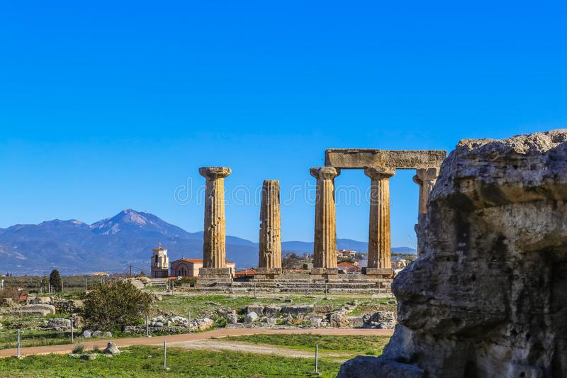 Säulen vom Tempel von Apollo in altem Korinth Griechenland und Hintergrund der lokalen malerischen Kirche und der mountians auf F lizenzfreie stockfotos