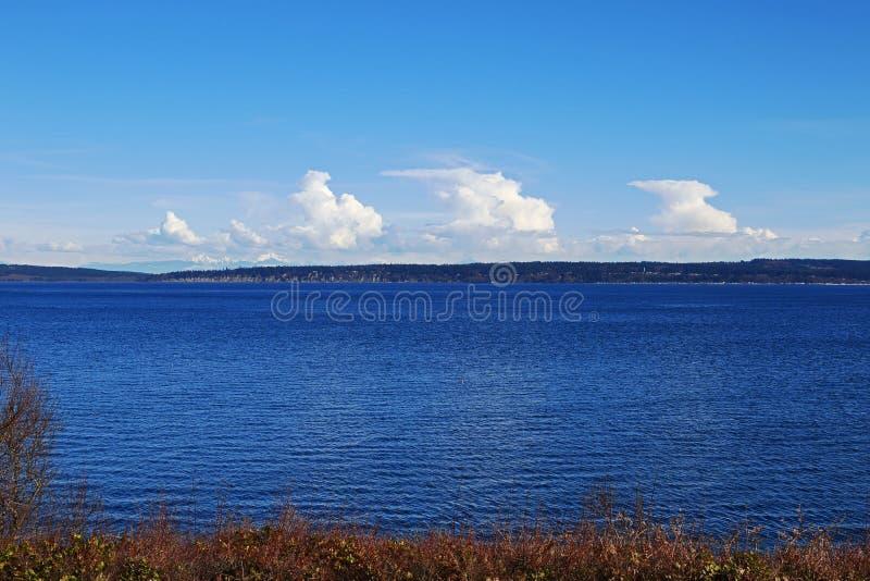 Säulen von weißen Wolken über Land und Meer lizenzfreie stockfotos