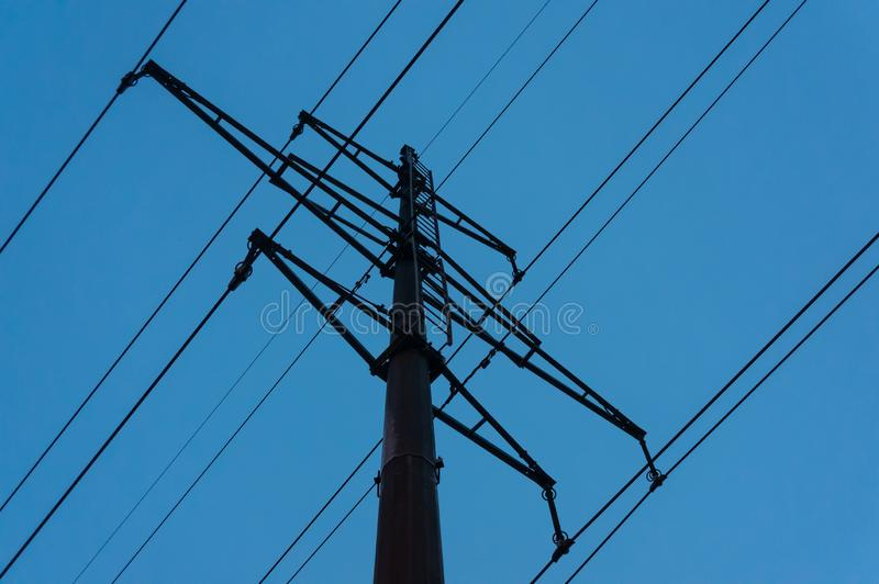 Säulenhochspannungsleitungen gegen den glättenden blauen Himmel stockfotos