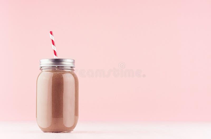 Słodkiej czekolady milkshake w staromodnych słojach z słomą, srebna nakrętka na lekkim pastelowych menchii tle zdjęcia stock