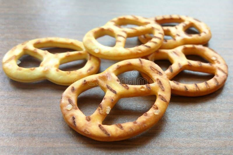 Słonego crispy krakersu mini precle na drewnianym stołowym tle zdjęcia stock