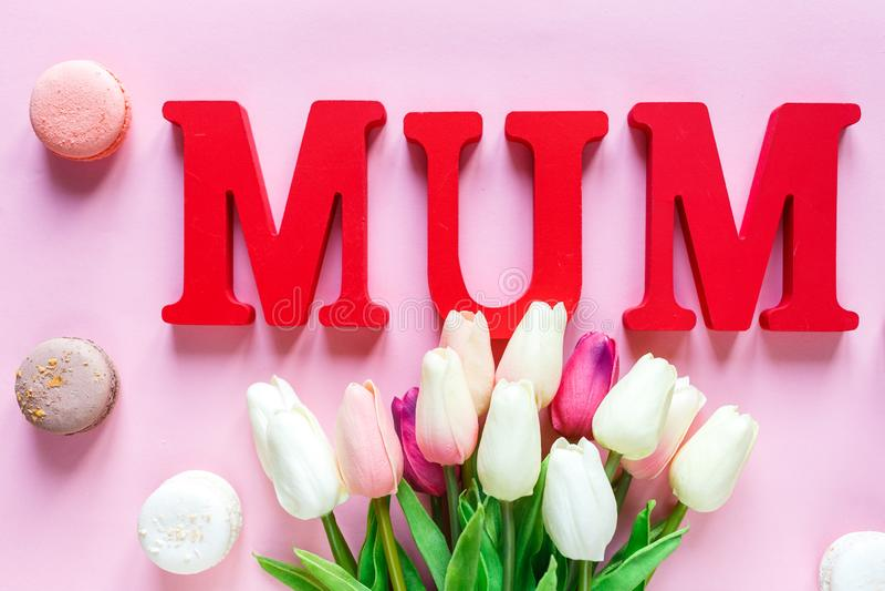 Słowa Mum od czerwień listów i czułych tulipanów, macaroons na różowym tle r Odgórny widok, mieszkanie nieatutowy obraz royalty free