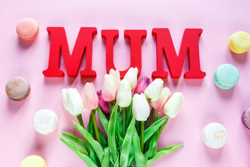 Słowa Mum od czerwień listów i czułych tulipanów, macaroons na różowym tle r Odgórny widok, mieszkanie nieatutowy obraz stock