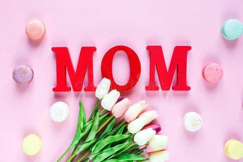 Słowo mama od czerwień listów i czułych tulipanów, macaroons na różowym tle r Odgórny widok, mieszkanie nieatutowy zdjęcie stock