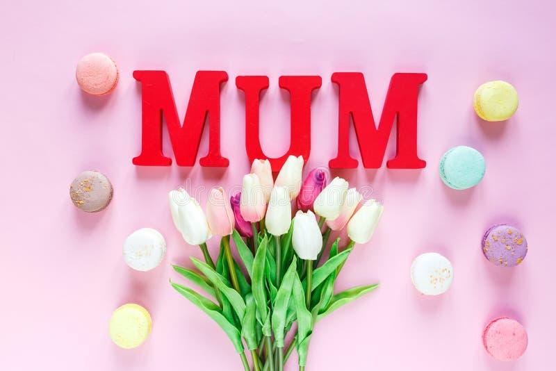 Słowo mama od czerwień listów i czułych tulipanów, macaroons na różowym tle r Odgórny widok, mieszkanie nieatutowy obraz stock