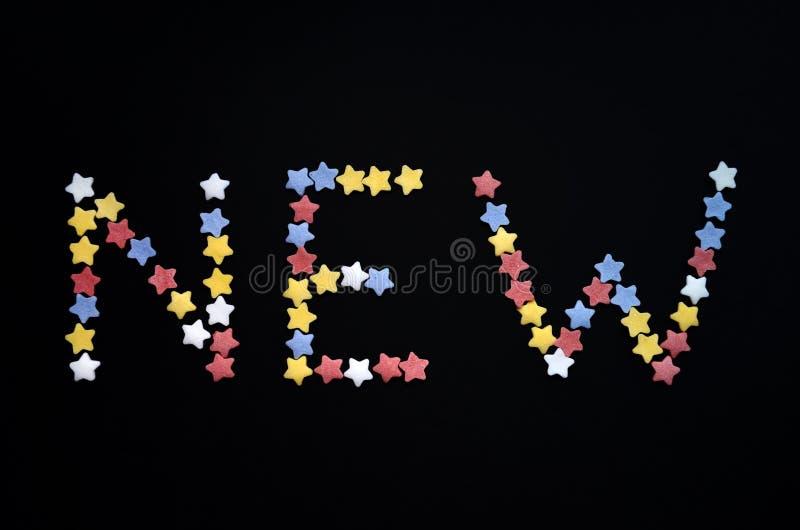 Słowo Nowy napisze w gęstym typie cukrowe ciasto gwiazdy na czarnym tle, dla, reklamuje, handel, sprzedaże zdjęcia stock