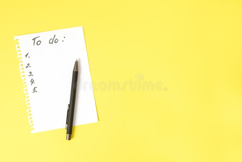 Så här gör du en lista på vitt ark som slits från spiral anteckningsbok och svart penna på ljusgult bord med kopieringsutrymme, ö royaltyfri foto