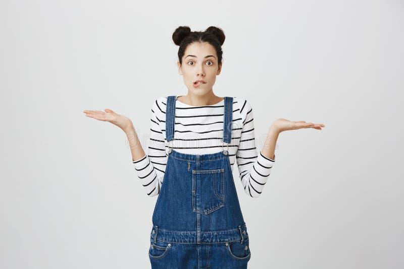 Så vad, som att bry sig Osäker tvivelaktigt stilfull grov bomullstvill för den unga kvinnan för brunetten bärande beklär att ryck royaltyfri bild