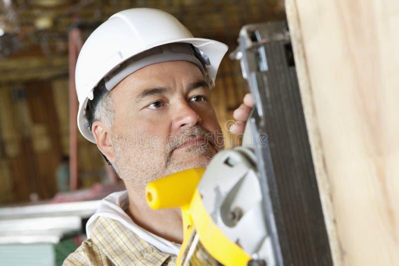 Såg bitande trä för den allvarliga manliga byggnadsarbetaren med en makt royaltyfri foto