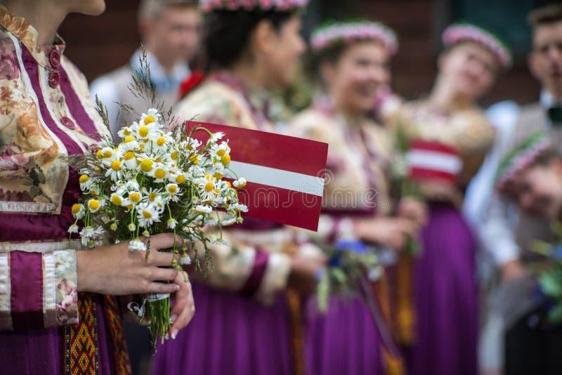 Sång- och dansfestival i Lettland Procession i Riga Beståndsdelar av prydnader och blommor Lettland 100 år arkivfoto