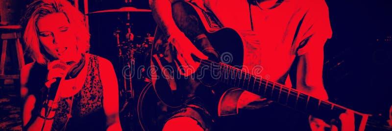 Sångare med gitarristen som rymmer den digitala minnestavlan på nattklubben royaltyfri bild
